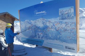 Skieurs devant le plan des pistes en haut de la station