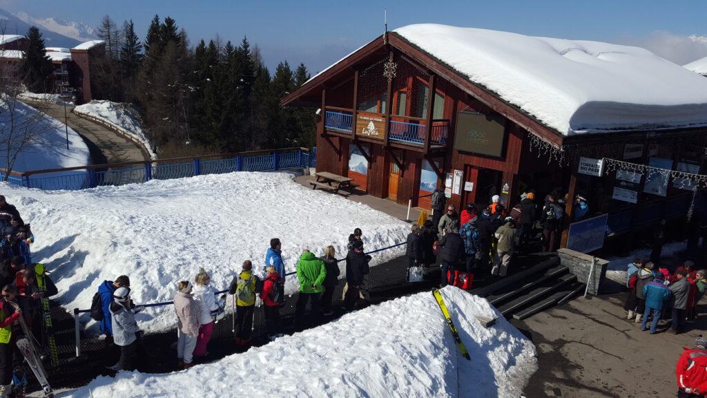 une longue file d'attente aux caisses des forfaits d'une station de ski, point de contact clé du parcours utilisateur